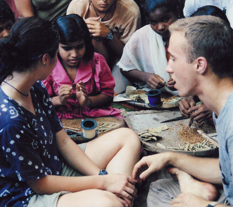 Craig sits with children in India