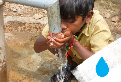 A young boy drinks water from a fountain