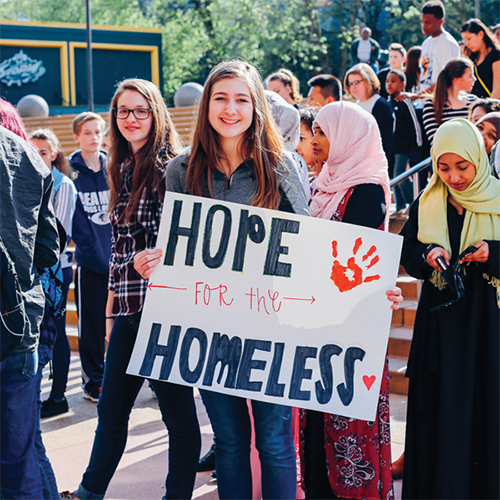 "A student holding a sign that reads ""Hope for the Homeless"""
