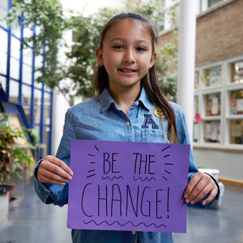 "A student holding a sin saying ""Be the change!"""