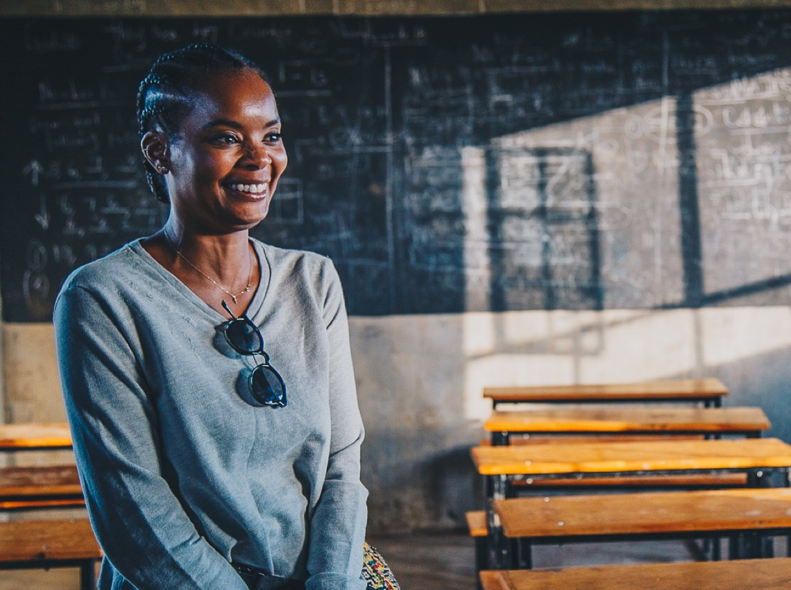A smiling woman sitting in a classroom full of desks and a chalkboard.