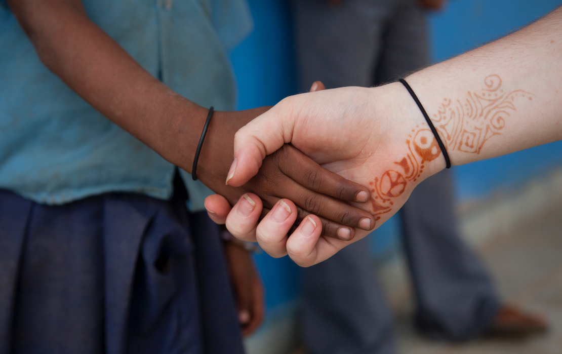 A volunteer holding a child's hand