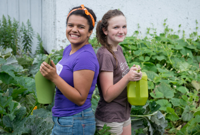 Two volunteers tending to a garden