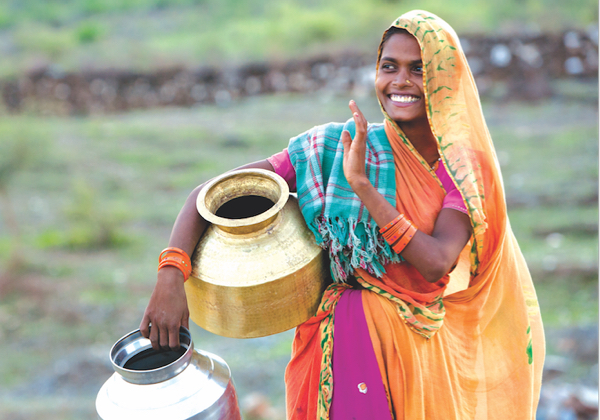 Lady in India carrying water jugs