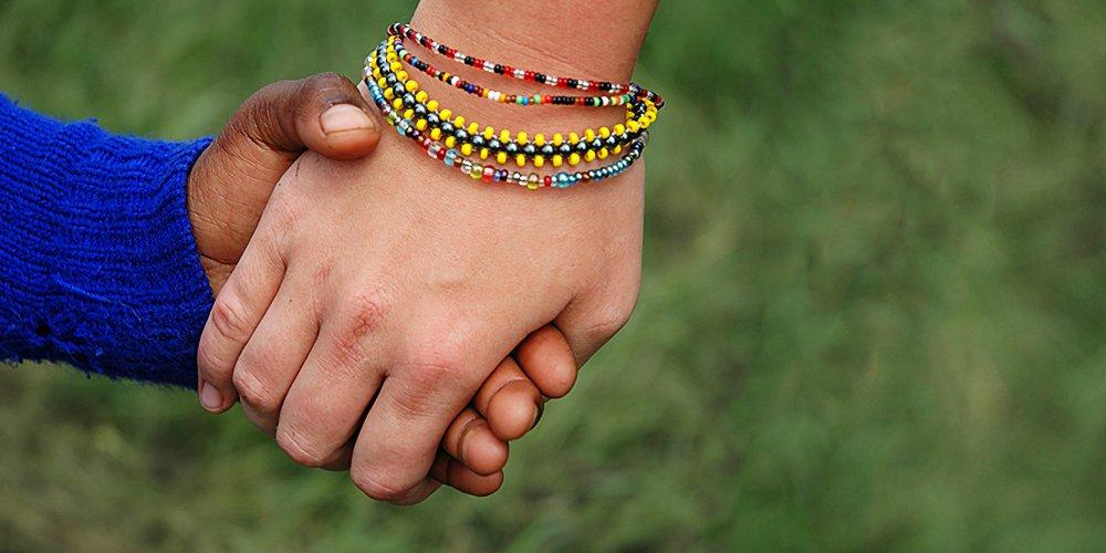 Un bénévole main dans la main avec un enfant